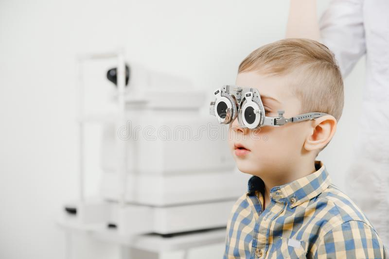 Kinderaufnahme-Doktoraugenarzt wählt Gläser der Linse, Kontrollaugenanblick vor lizenzfreie stockfotografie