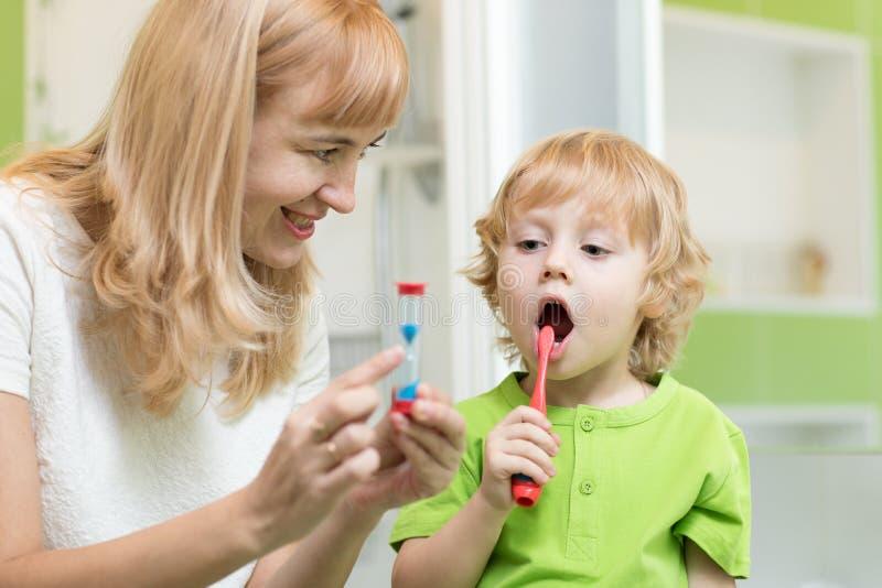 Kinderbürstende Zähne nähern sich Spiegel im Badezimmer Seine Mutterüberwachungsgenauigkeit und Zeit der Reinigungsaktion mit San lizenzfreie stockfotos