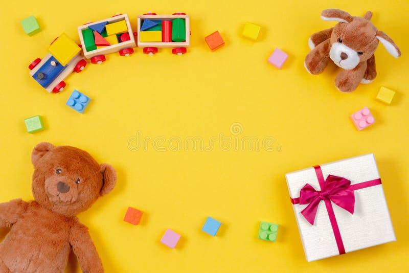 Kinderbaby-Spielzeughintergrund Teddybär, Spielzeugzug, anwesende Geschenkbox und andere Spielwaren auf gelbem Hintergrund stockbild