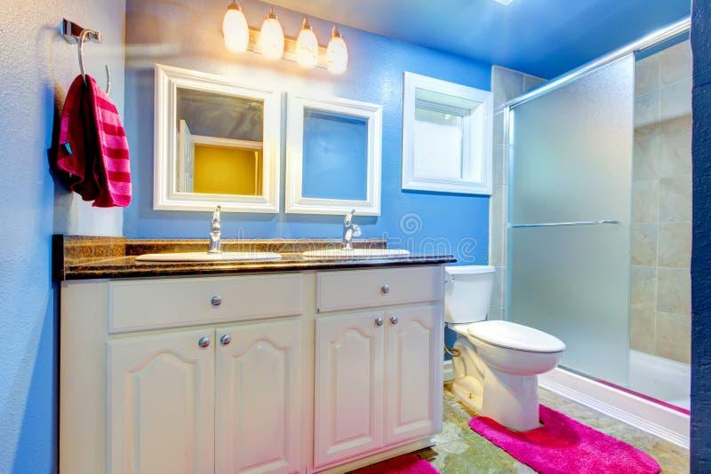 Kinderbadezimmer mit blauen Wänden und rosa Wolldecke und Tuch stockfotografie