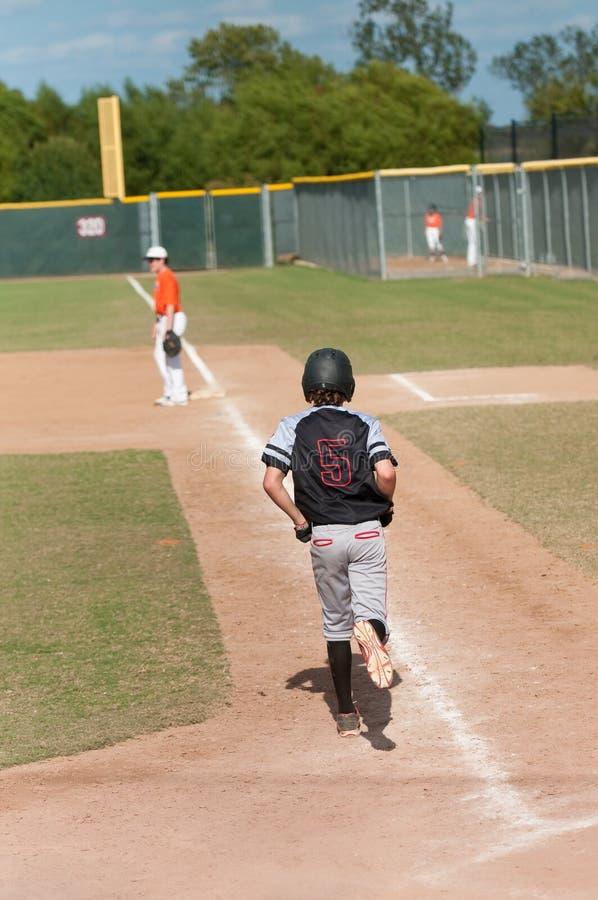 Kinderbaseball-spieler, der erste Base nimmt stockfoto