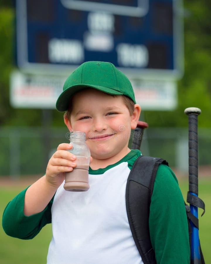 Kinderbaseball-spieler-Trinkschokolademilch lizenzfreie stockfotografie