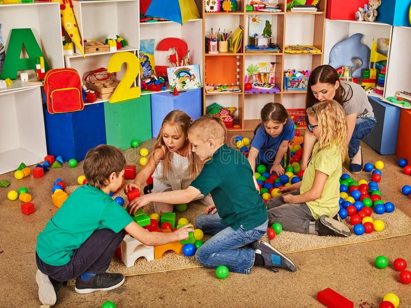 Kinderbausteine im Kindergarten Gruppenkinder, die Spielzeugboden spielen stockbild