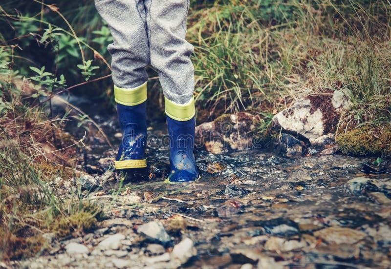 Kinderbeine in den Gummistiefeln in den Waldnebenfluß stockfoto