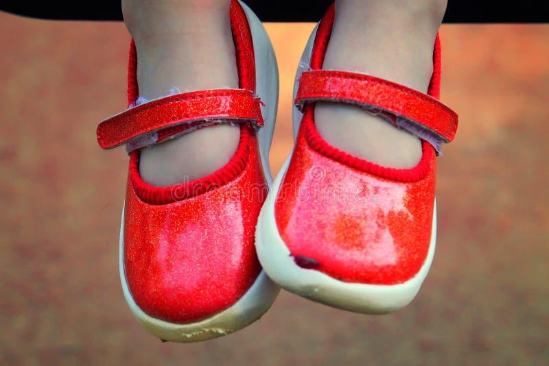 Kinderbeine in den roten Schuhen stockfotos