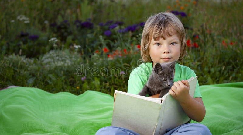 Kinderboek lezen met Cat in de tuin, Jongen met kattenpeuterblad op het gras in het park. stock afbeeldingen