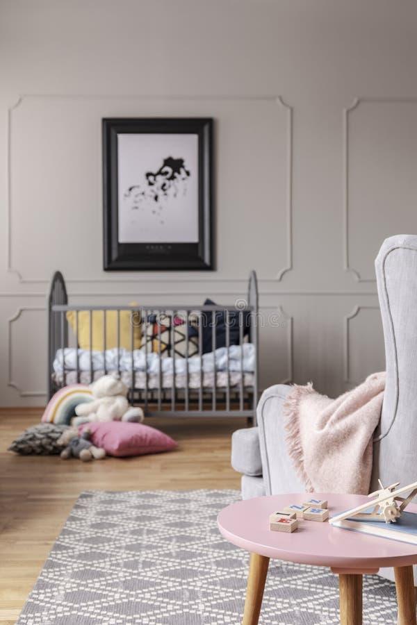 Kinderdagverblijf met houten voederbak met kussens, echte foto met model op de grijze muur stock fotografie