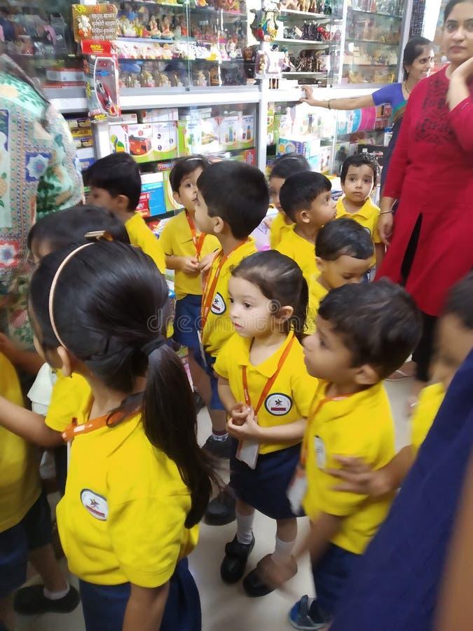 Kinderdagverblijfjonge geitjes van school het bezoeken winkels, ATM, enz. om erkend te worden van varoous sociale instelling royalty-vrije stock afbeelding