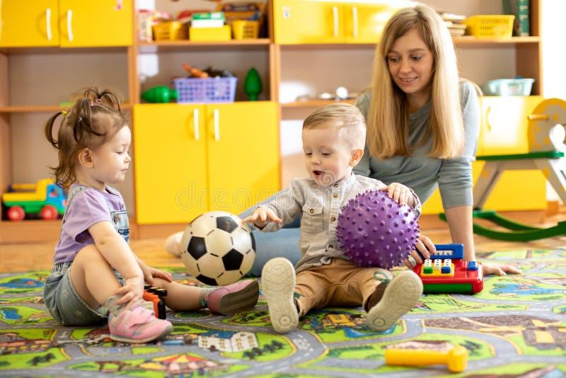 Kinderdagverblijfleraar die voor kinderen in kleuterschool zorgen Het kleine spel van jonge geitjespeuters samen met speelgoed royalty-vrije stock afbeelding