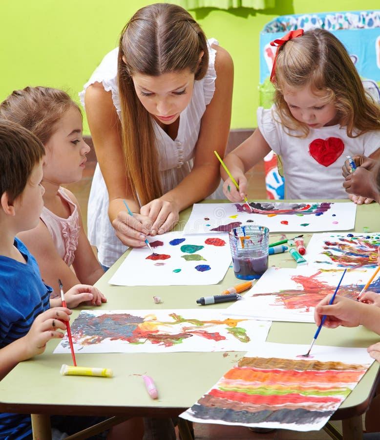 Kinderdagverblijfleraar het schilderen stock foto's