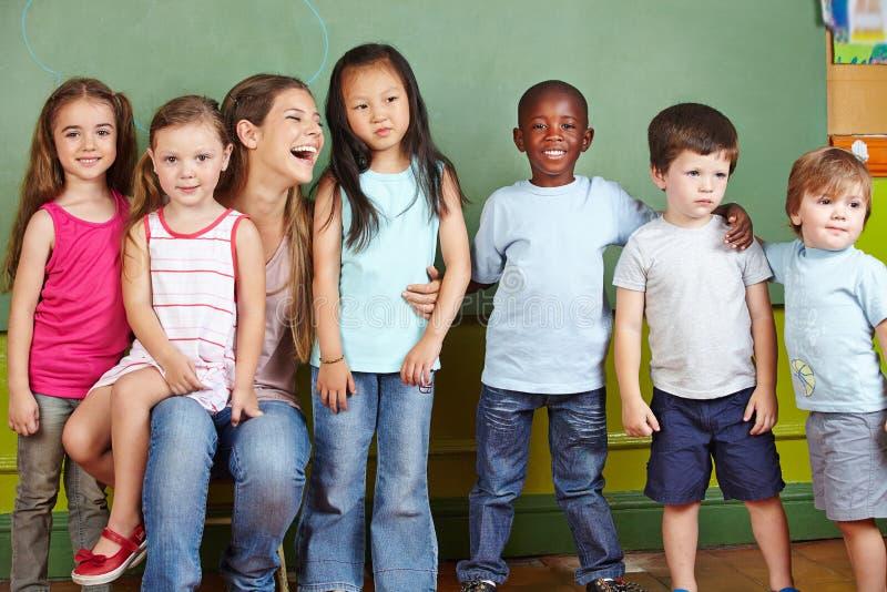Kinderdagverblijfleraar met kinderen stock afbeelding