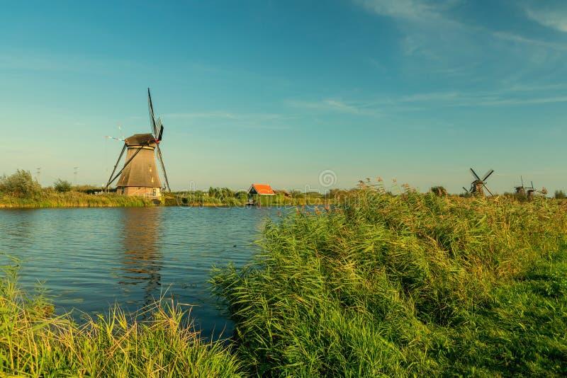 Kinderdijk kanaler med väderkvarnar Solnedgång i den mer snälla holländska byn arkivfoto