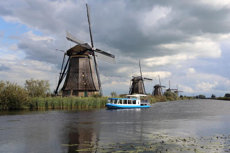 Windmills and tourboat at Kinderijk, Holland royalty free stock image