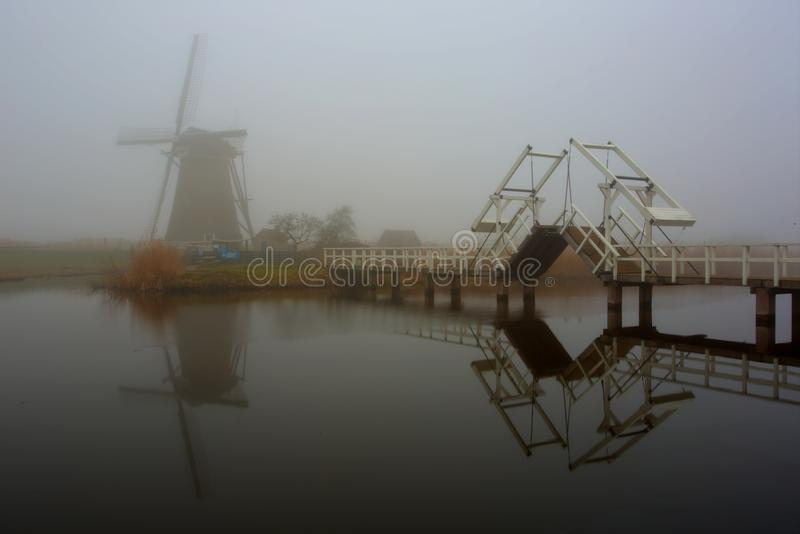 Kinderdijk, reflection of a windmill. A windmill and a bridge in the morning mist at Kinderdijk, South Holland
