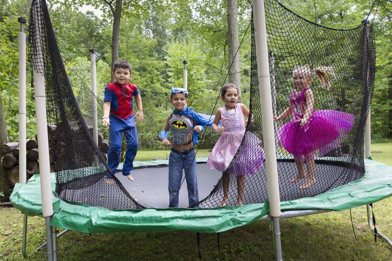 Kinderen als super-helden worden vermomd of prinsessen die op trampoline springen die royalty-vrije stock foto's