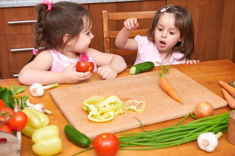 Kinderen bij de lijst met met verse vruchten en groenten, binnenlands, gezond het voedselconcept van de huiskeuken royalty-vrije stock afbeeldingen