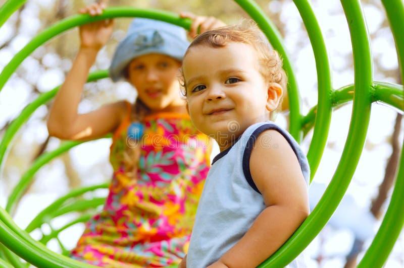 Kinderen bij de speelplaats stock afbeeldingen