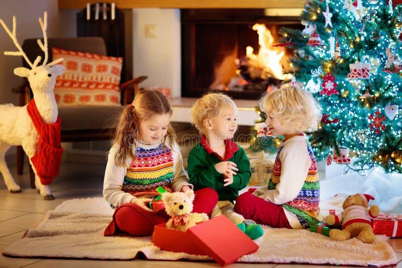 Kinderen bij Kerstboom en open haard op Kerstmisvooravond Familie die met jonge geitjes Kerstmis thuis vieren  stock fotografie