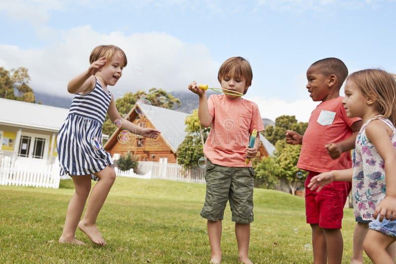 Kinderen bij Montessori-School het Spelen met Bellen tijdens Onderbreking stock afbeeldingen