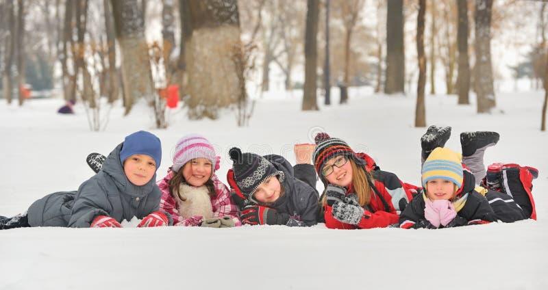Kinderen in de sneeuw in de winter stock afbeelding