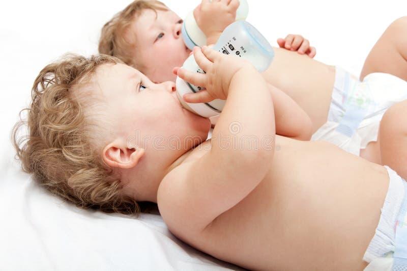 Kinderen de tweelingen die zuigen melkflessen liggen stock foto's