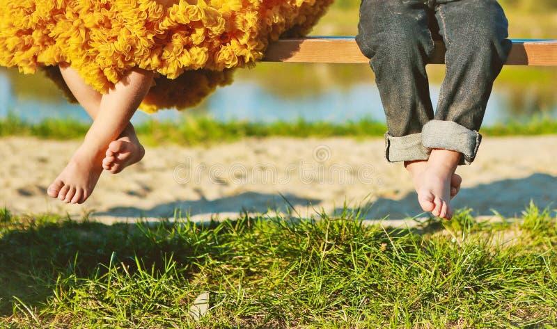 Kinderen dichtbij het gras van de de benenlente van het jongensmeisje royalty-vrije stock foto