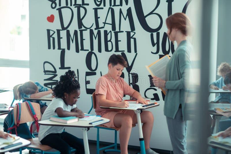 Kinderen die aan hun test in het klaslokaal werken stock fotografie