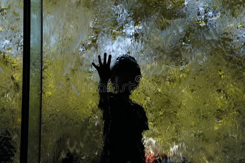 Kinderen die achter water en glasgordijn spelen stock afbeelding