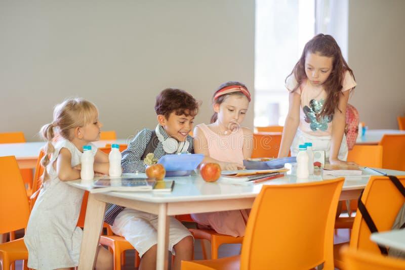 Kinderen die bezig terwijl het leren van gedicht en het eten van lunch voelen royalty-vrije stock afbeeldingen