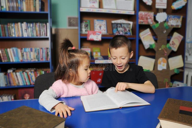 Kinderen die in bibliotheek interessant boek lezen Meisje en jongens het leren royalty-vrije stock afbeeldingen