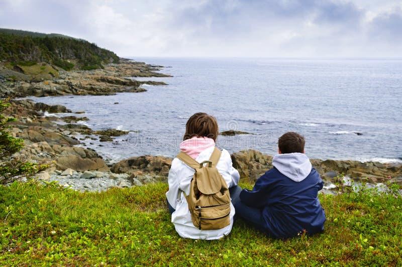 Kinderen die bij Atlantische kust in Newfoundland zitten stock fotografie