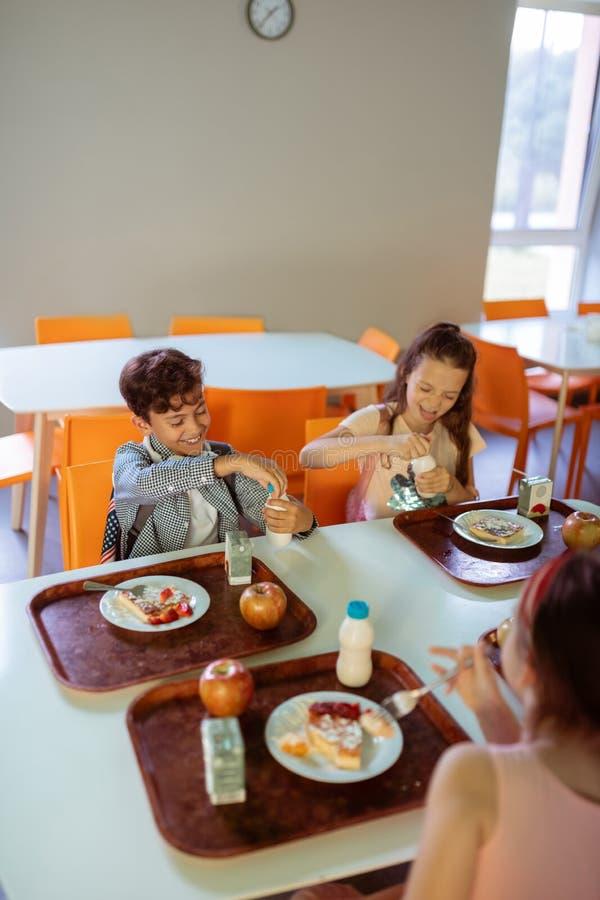 Kinderen die bij de lijst met dienbladen van voedsel zitten terwijl het hebben van lunch stock foto