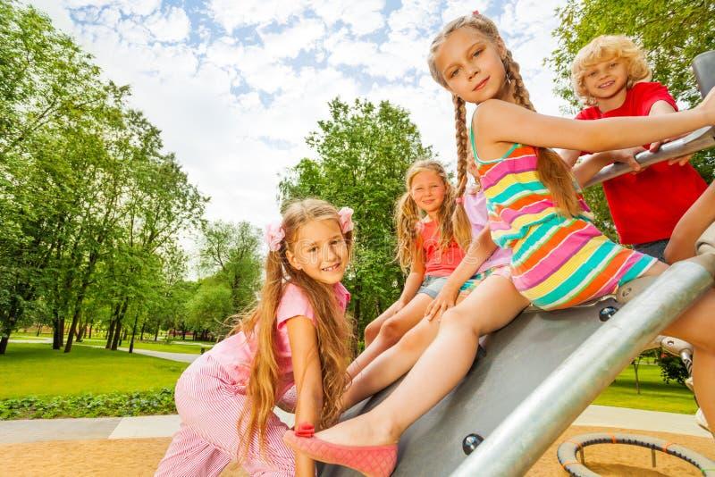 Kinderen die bij de speelplaatsbouw zitten stock foto's