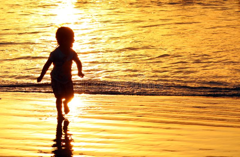 Kinderen die bij het strand in Bali, Indonesië tijdens een gouden zonsondergang spelen Oceaan zoals goud royalty-vrije stock foto's