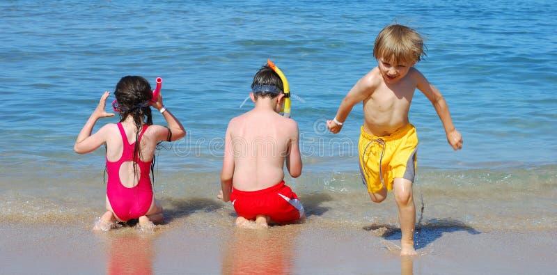 Kinderen die bij het strand spelen royalty-vrije stock afbeeldingen