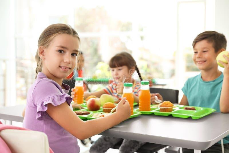 Kinderen die bij lijst zitten en gezond voedsel eten tijdens onderbreking stock afbeeldingen