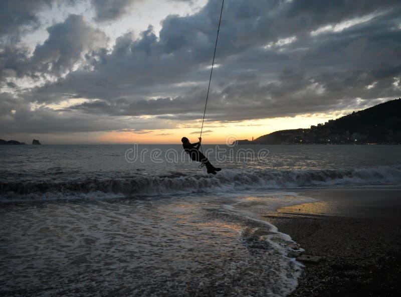 Kinderen die bij Zonsondergang door het overzees spelen royalty-vrije stock afbeeldingen