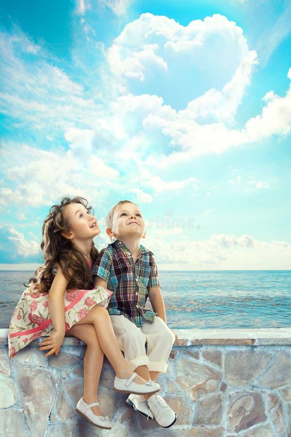 Kinderen die blauwe hemel met hart gevormde wolken kijken stock afbeeldingen