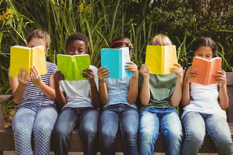 Kinderen die boeken lezen bij park stock afbeeldingen