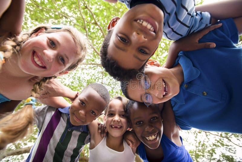 Kinderen die in cirkel rond de camera omhelzen stock fotografie