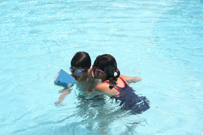 Kinderen die in de pool spelen stock foto's