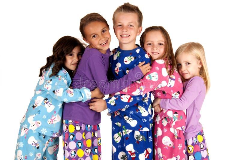 Kinderen die in de pyjama's van vakantiekerstmis koesteren stock foto
