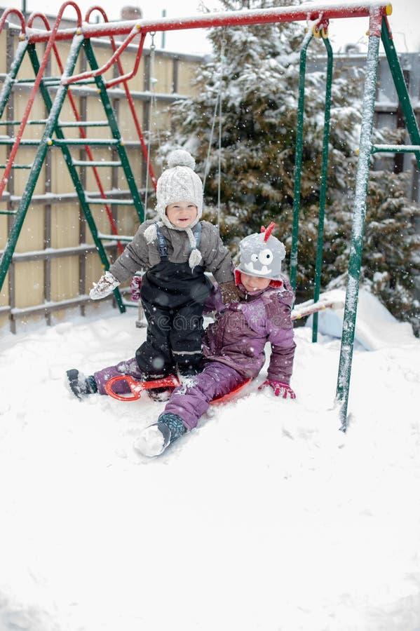 Kinderen die in de sneeuw spelen stock fotografie
