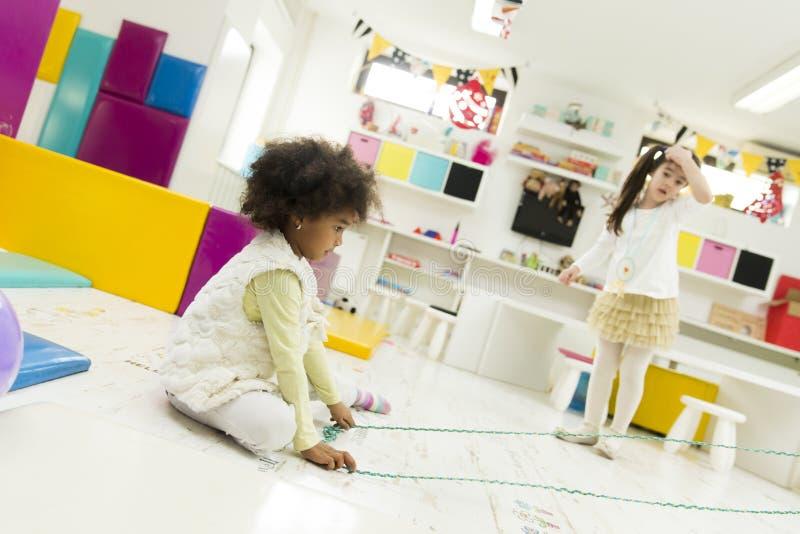 Kinderen die in de speelkamer spelen stock fotografie