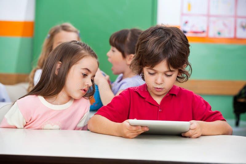 Kinderen die Digitale Tablet gebruiken bij Kleuterschool stock afbeelding
