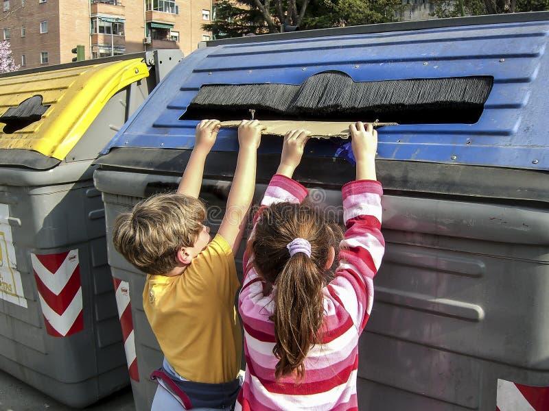 Kinderen die een karton trekken in het recycling van container voor document royalty-vrije stock foto's