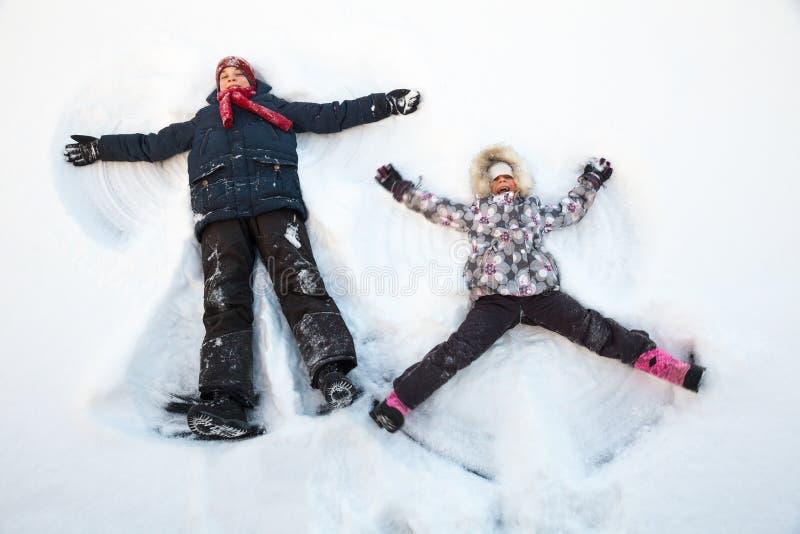 Kinderen die in een sneeuw spelen die van de winter genieten stock fotografie