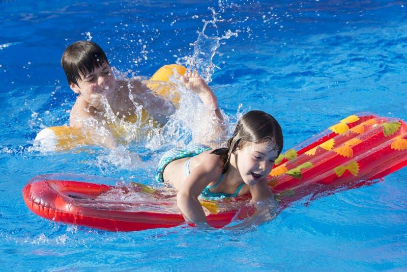 Kinderen die in een zwembad spelen stock afbeeldingen