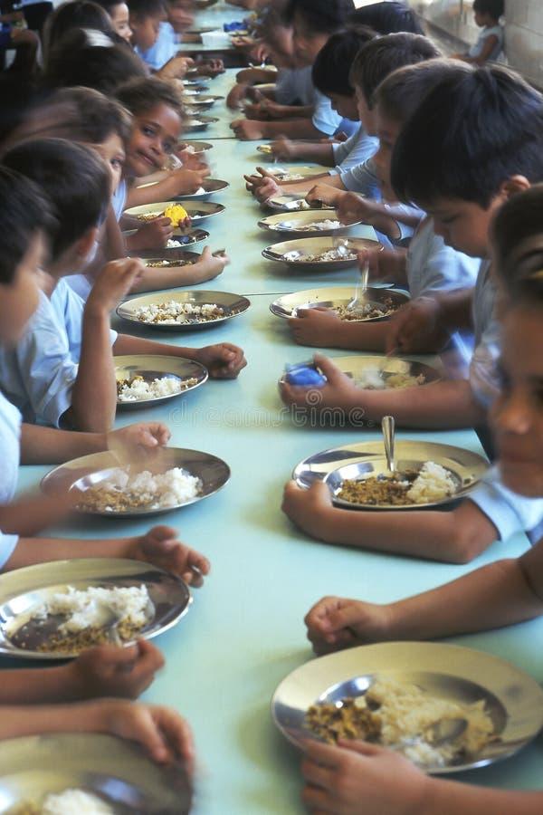 Kinderen die in eetzaal, Brazilië eten stock foto's
