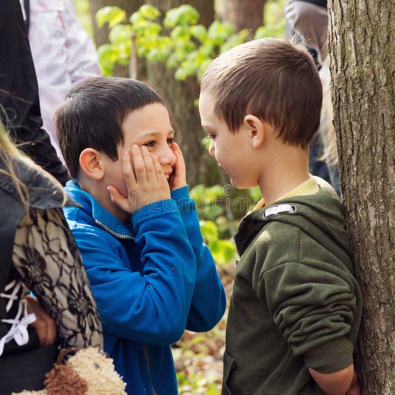 Kinderen die en in aard communiceren spelen stock foto